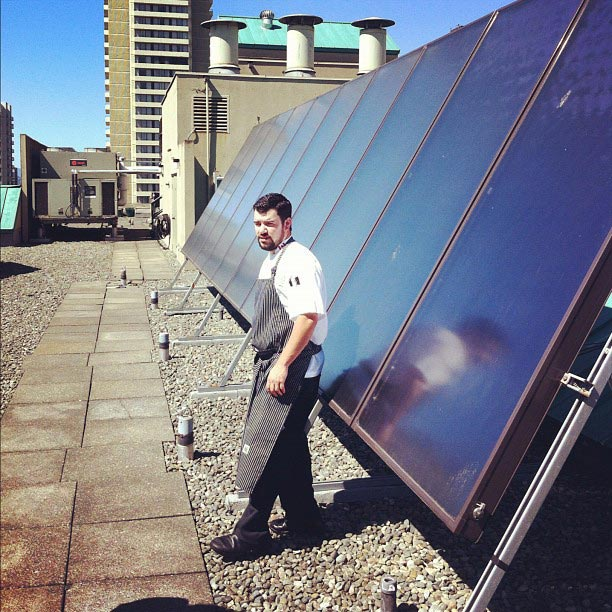 Chef Chris Whittaker atop the Listel Hotel with the restaurant's solar panels - Photo Credit: Forage